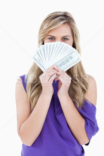 Blonde woman hiding her face behind a fan of notes against a white background Stock photo © wavebreak_media