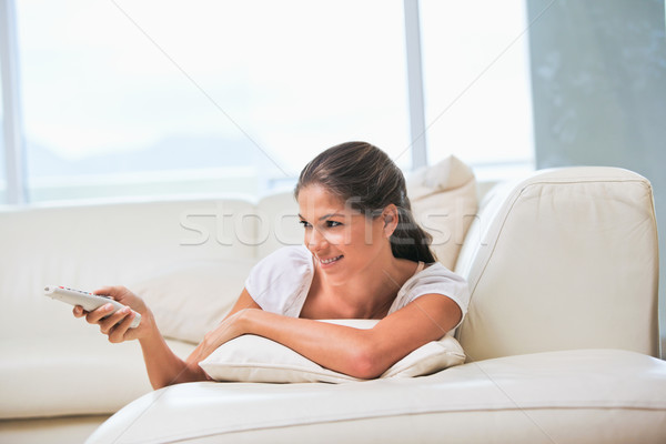 Woman lying on a sofa while holding a remote in a sitting room Stock photo © wavebreak_media