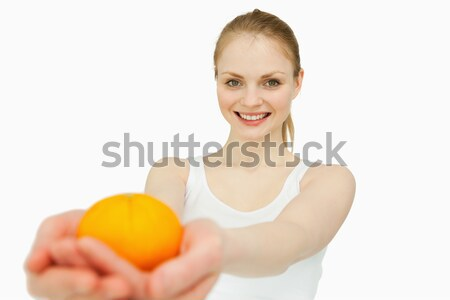 Joyful woman presenting a tangerine against white background Stock photo © wavebreak_media