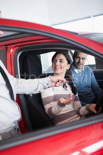 Smiling woman receiving keys from a salesman while sitting in a car Stock photo © wavebreak_media