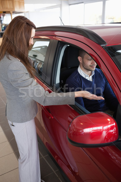 Stock photo: Woman presenting something to a client in a dealership