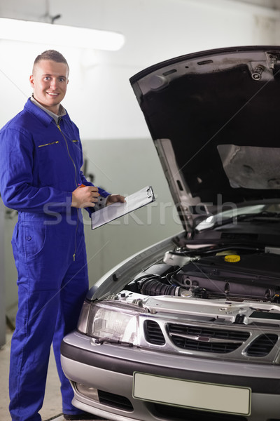 Smiling mechanic holding a clipboard and a pen in a garage Stock photo © wavebreak_media