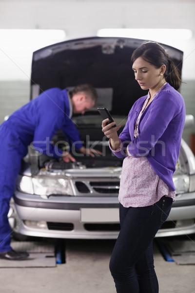 Kobieta patrząc telefonu komórkowego mechanik garaż samochodu Zdjęcia stock © wavebreak_media