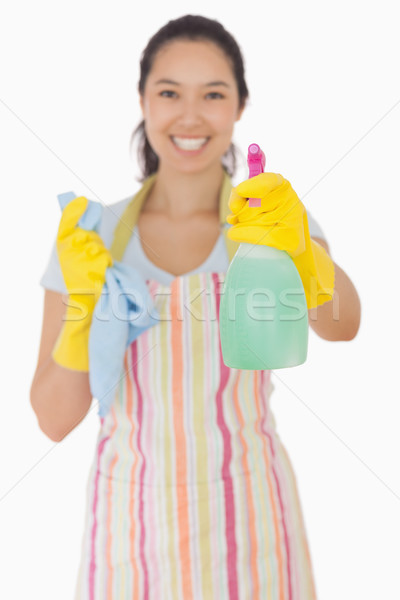 Happy woman in apron and rubber gloves holding out spray bottle Stock photo © wavebreak_media
