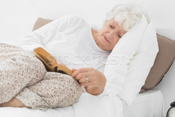 Old woman lying on the bed and reading Stock photo © wavebreak_media