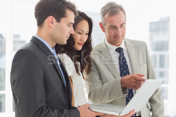 Foto stock: Equipe · de · negócios · olhando · laptop · juntos · escritório · negócio