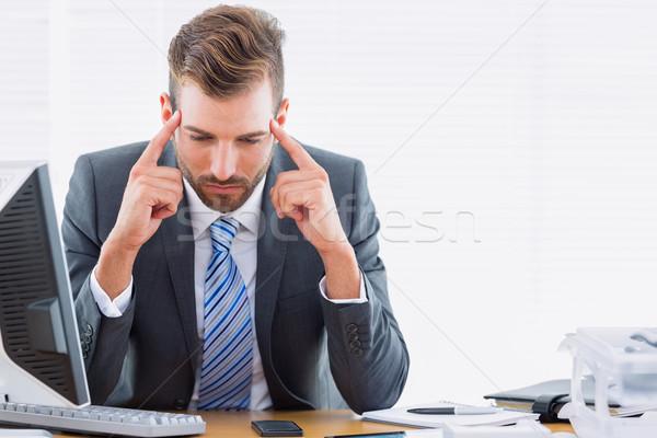 Empresário dor de cabeça sessão mesa de escritório jovem elegante Foto stock © wavebreak_media