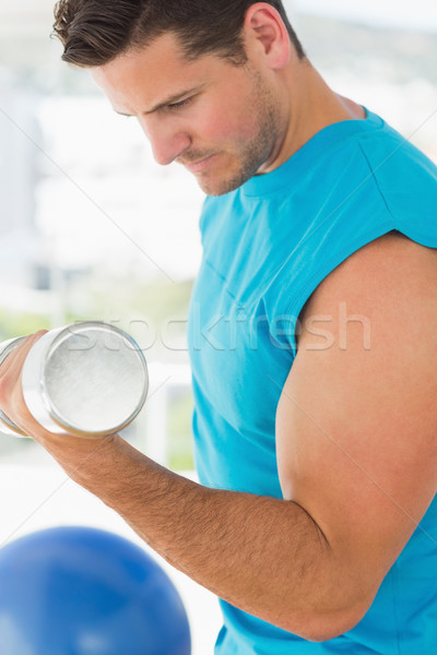 Sporty young man with dumbbell in gym Stock photo © wavebreak_media