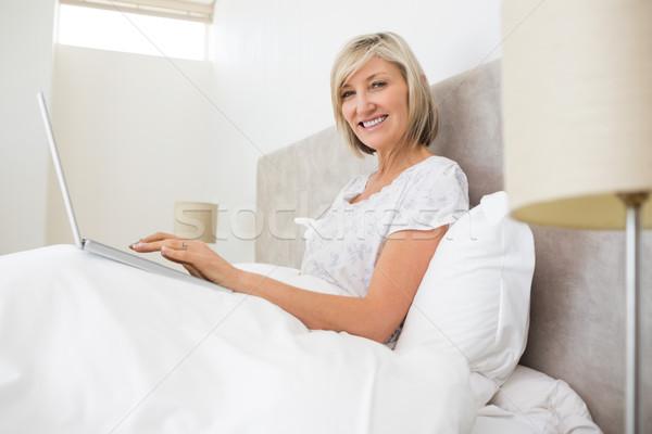 肖像 笑顔の女性 ラップトップを使用して ベッド 笑みを浮かべて 成熟した女性 ストックフォト © wavebreak_media