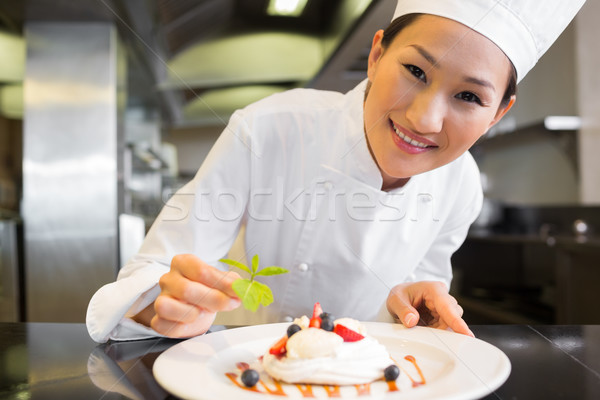 Smiling female chef garnishing food in kitchen Stock photo © wavebreak_media