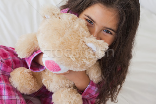 Gülen kız doldurulmuş oyuncak oturma yatak Stok fotoğraf © wavebreak_media