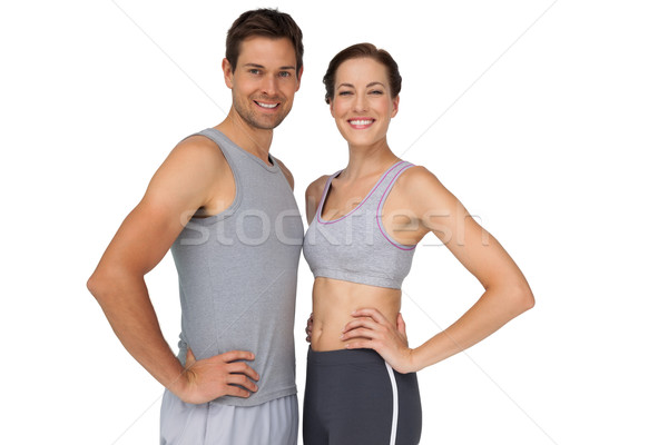 Portrait of a happy fit couple with hands on hips Stock photo © wavebreak_media