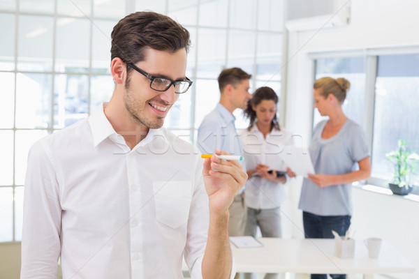 Stock photo: Casual businessman smiling at his electronic cigarette