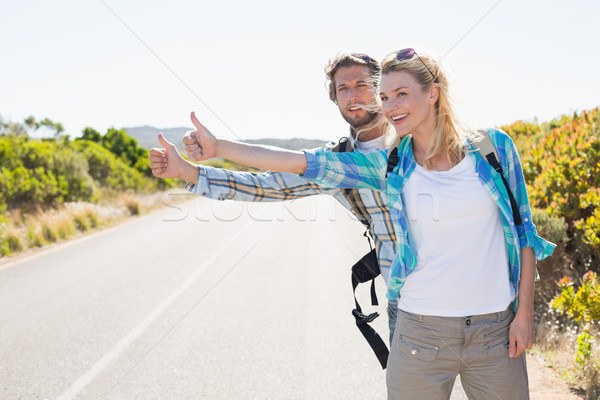 Stock photo: Attractive couple standing on the road hitch hiking