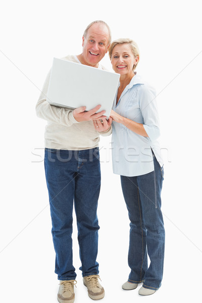 Mature couple smiling at camera with laptop Stock photo © wavebreak_media