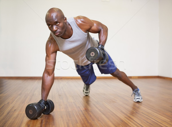 Muscular man doing push ups with dumbbells in gym Stock photo © wavebreak_media