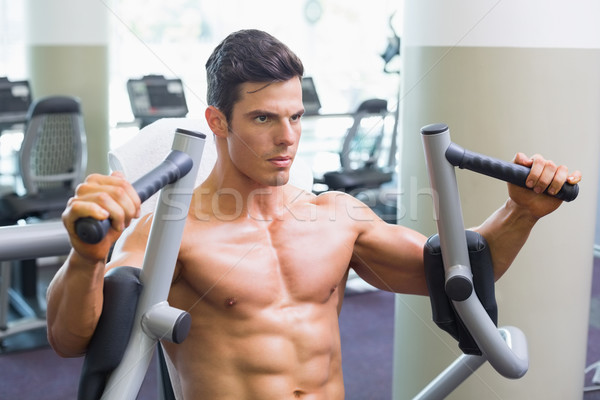 Muscular man working on fitness machine at the gym Stock photo © wavebreak_media