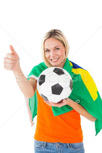 Football fan holding ball and wearing brazil flag Stock photo © wavebreak_media