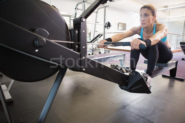 Woman working on fitness machine at gym Stock photo © wavebreak_media