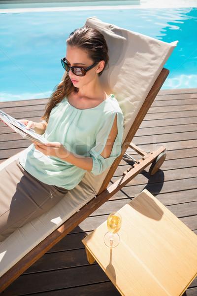 Kobieta czytania książki basen szampana tabeli Zdjęcia stock © wavebreak_media