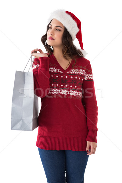 Thoughful brunette in santa hat holding shopping bag Stock photo © wavebreak_media