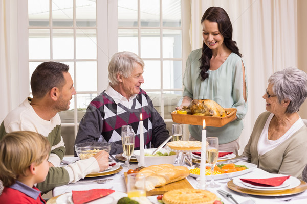 Woman holding turkey roast with family at dining table Stock photo © wavebreak_media