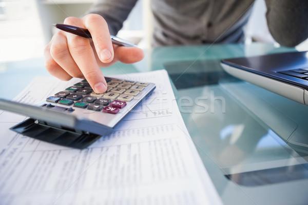 Casual businessman calculating his expenses  Stock photo © wavebreak_media