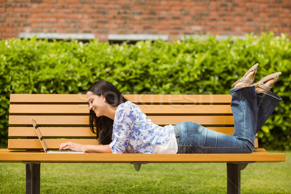 Cool brunette lying on bench using laptop Stock photo © wavebreak_media