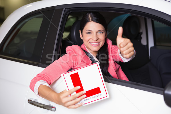 Woman gesturing thumbs up holding a learner driver sign Stock photo © wavebreak_media