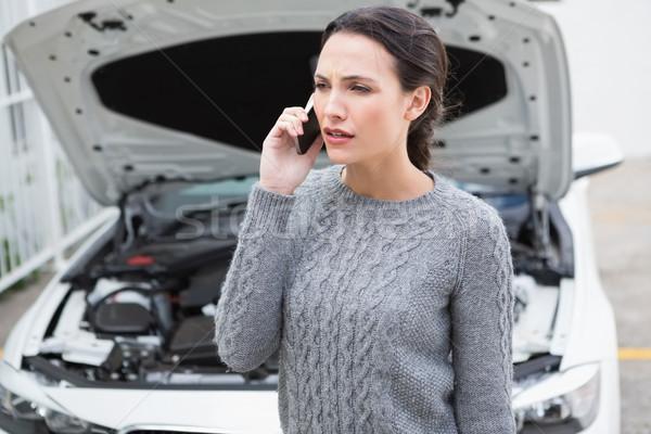 Annoyed woman on the phone beside her broken down car Stock photo © wavebreak_media