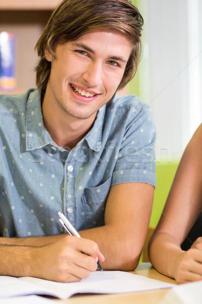Stockfoto: Gelukkig · mannelijke · student · huiswerk · bibliotheek · portret
