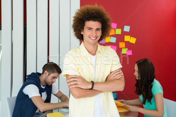 Casual young man with arms crossed in office Stock photo © wavebreak_media
