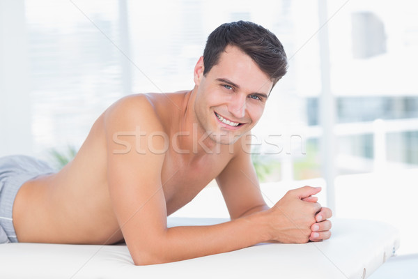 Smiling patient lying on massage table and looking at camera Stock photo © wavebreak_media