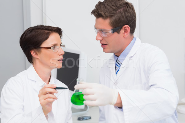 Scientists examining attentively beaker with green fluid Stock photo © wavebreak_media