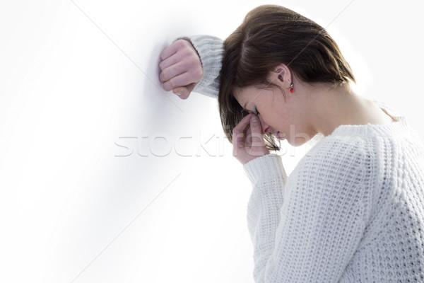 Sad pretty brunette leaning against wall Stock photo © wavebreak_media