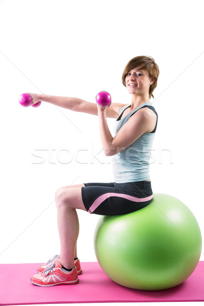 Pretty brunette exercising with dumbbells on fitness ball  Stock photo © wavebreak_media