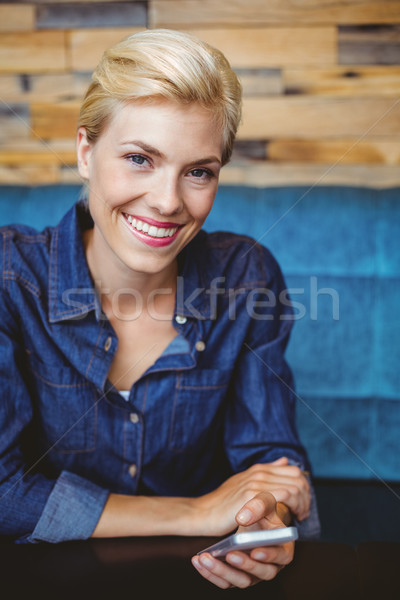 Smiling pretty blonde sending a text message Stock photo © wavebreak_media
