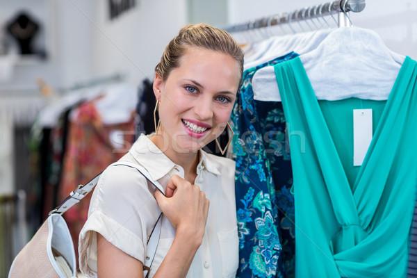 Smiling woman standing next to clothes rail Stock photo © wavebreak_media