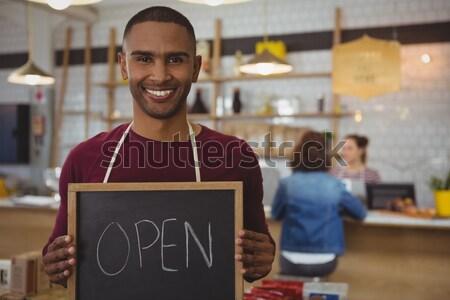 Smiling waiter showing chalkboard with open sign Stock photo © wavebreak_media
