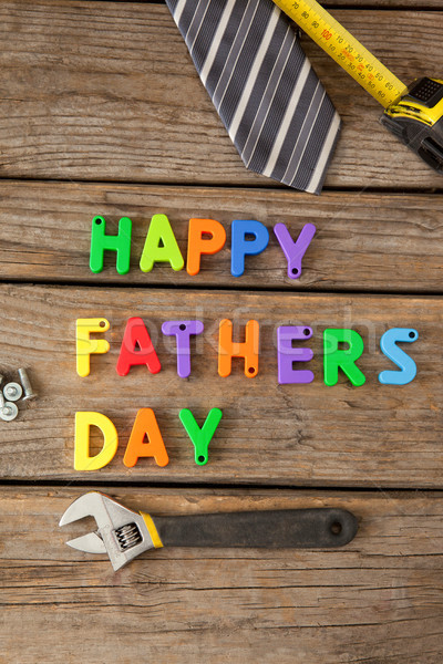 Happy fathers day blocks, tie, measuring tape and handtools on wooden plank Stock photo © wavebreak_media
