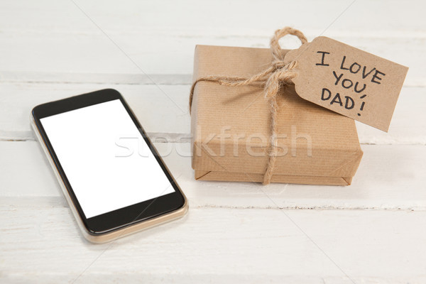 Mobile phone and gift box on wooden plank Stock photo © wavebreak_media