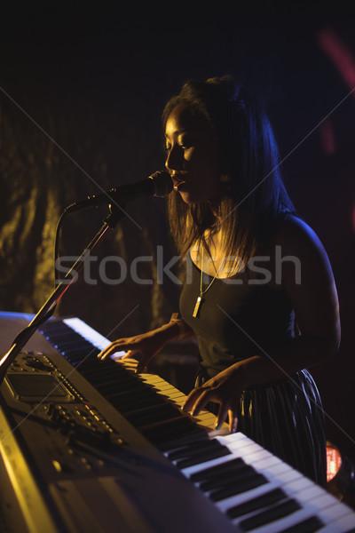 Femenino jugando piano cantando iluminado discoteca Foto stock © wavebreak_media