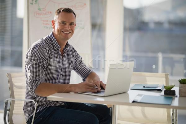 Portrait of confident executive using laptop at desk Stock photo © wavebreak_media