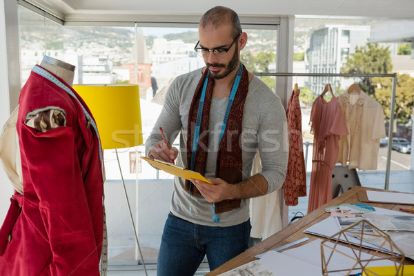 Designer writing on paper while standing by mannequin Stock photo © wavebreak_media