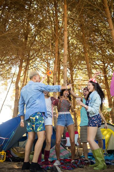 Cheerful male friends toasting beer bottles at campsite Stock photo © wavebreak_media