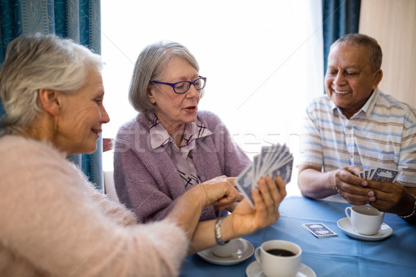 Smiling senior woman showing cards to friends while playing Stock photo © wavebreak_media