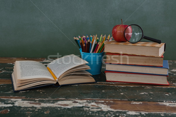 Stock photo: Stack of books with apple, magnifying glass and pen holder
