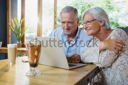 Father and son sitting on sofa with laptop and book in living room Stock photo © wavebreak_media