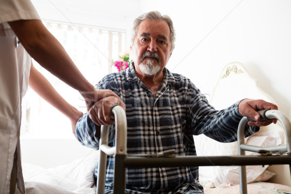 Female doctor standing by senior man holding walker in nursing home Stock photo © wavebreak_media