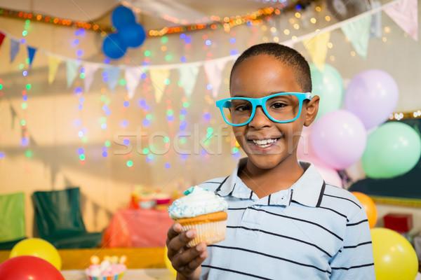 Portrait of cute boy holding cupcake during birthday party Stock photo © wavebreak_media